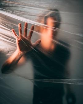 Homem atrás de um saco plástico tocando-o com a palma da mão