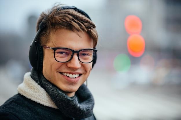Homem atrativo alegre que escuta a música nos fones de ouvido, ao ar livre.