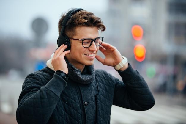 Homem atrativo contente que escuta a música nos auscultadores, apreciando, andando na rua.