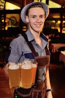 Homem atrativo na roupa bávara tradicional e em um chapéu.