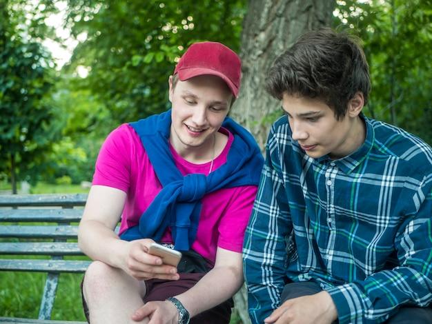 Homem atrativo novo que mostra a notícia alimenta no telefone a seu irmão mais novo no parque