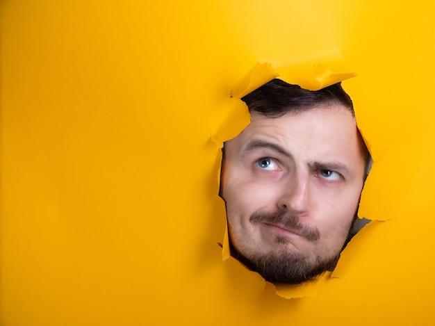 Homem através de um buraco de papel amarelo pensando