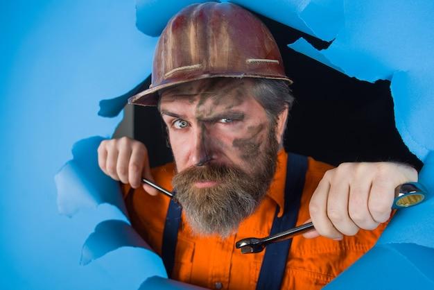 Homem através do trabalhador de publicidade em papel segura a chave inglesa, chaves de fenda, ferramentas de reparo, trabalhador barbudo, através