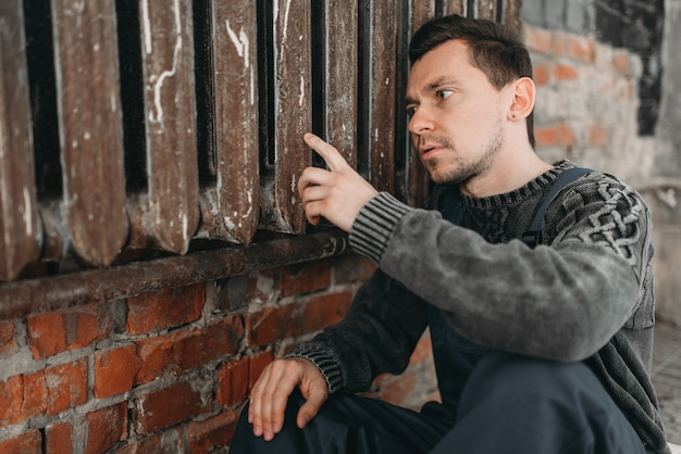 Homem autista sozinho sentado no radiador enferrujado.