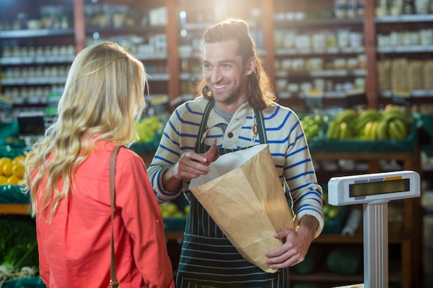 Homem, auxiliando a mulher na seleção de legumes