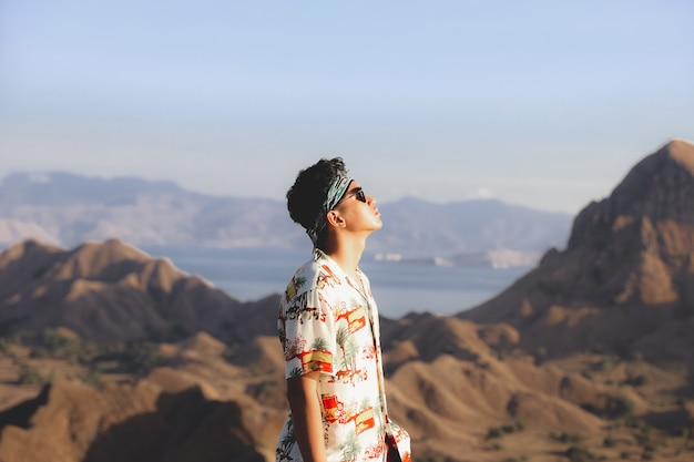Homem aventureiro asiático com bandana posando com fundo de colinas