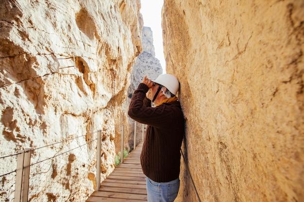 Homem aventureiro de meia idade com capacete usando binóculos em suas férias em uma expedição de montanha