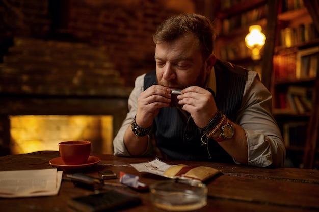 Homem babando cigarro enrolado à mão, mesa de madeira. cultura de fumar tabaco, sabor rico específico. fumante masculino lazer no escritório