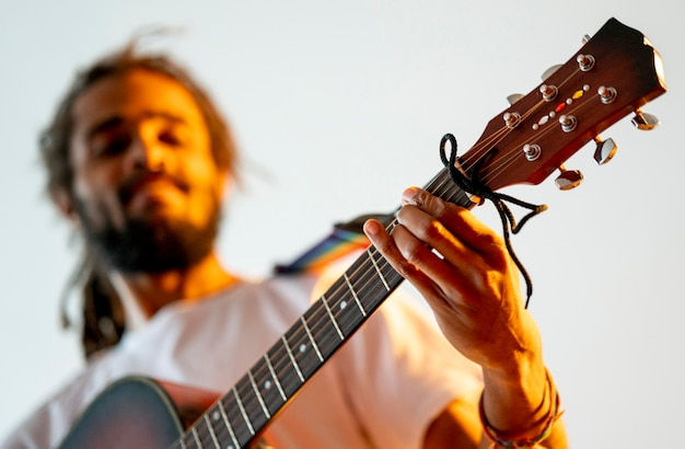 Homem baixo ângulo, tocando violão