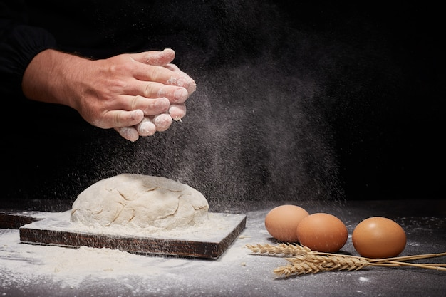 Homem baker e as mãos sobre o pão de farinha de trigo integral