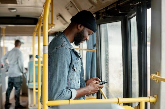 Homem baleado médio com telefone viajando de ônibus