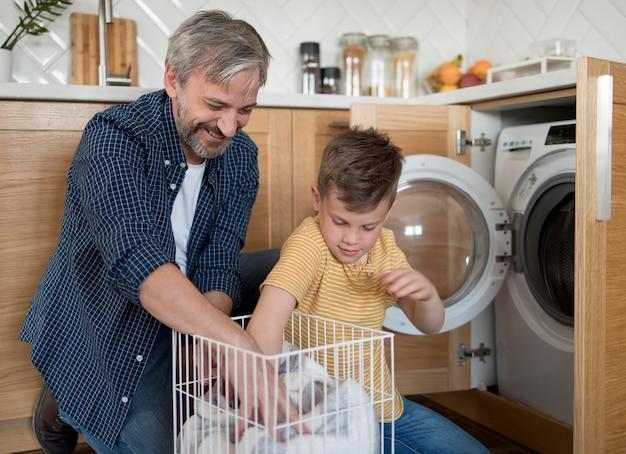 Homem baleado médio e filho lavando roupa