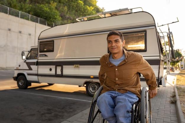 Homem baleado médio em cadeira de rodas ao ar livre