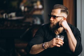 Homem barbado bebendo em um bar