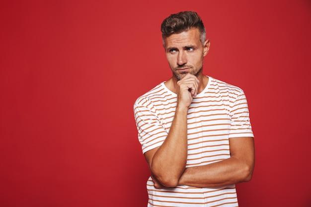 Homem barbado em uma camiseta listrada pensando e tocando o queixo isolado no vermelho