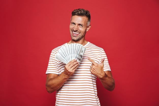 Homem barbado em uma camiseta listrada sorrindo e segurando um leque de dinheiro em dinheiro isolado no vermelho