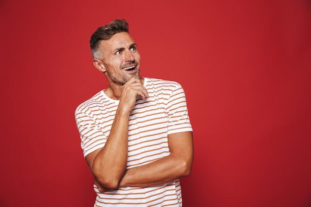 Homem barbado em uma camiseta listrada tocando o queixo e olhando de lado para copyspace isolado no vermelho
