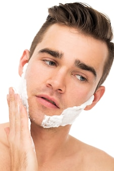 Homem barbeando o rosto com espuma