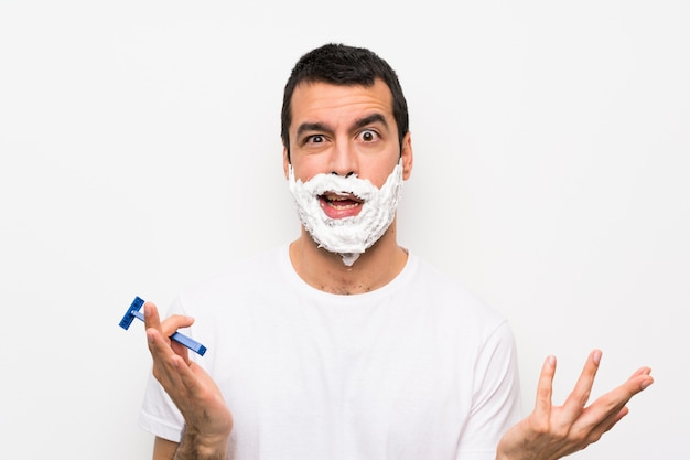 Homem barbear a barba sobre parede branca isolada, fazendo o gesto de dúvidas