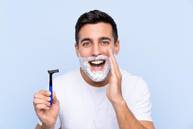 Homem barbear a barba sobre parede isolada