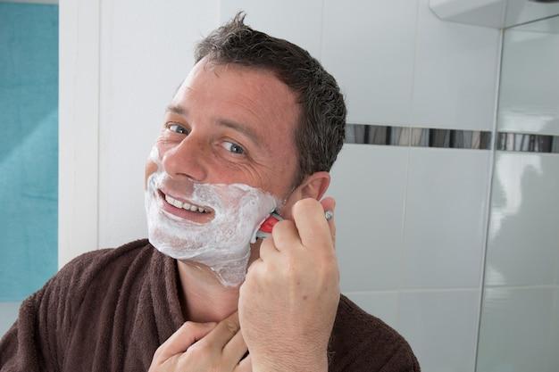 Homem barbear com uma lâmina de barbear e creme de barbear no banheiro