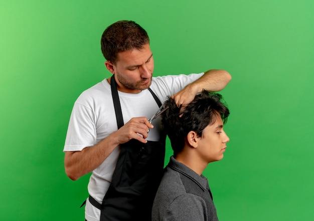 Homem barbeiro com avental cortando cabelo com uma tesoura de cliente satisfeito em pé sobre a parede verde 3