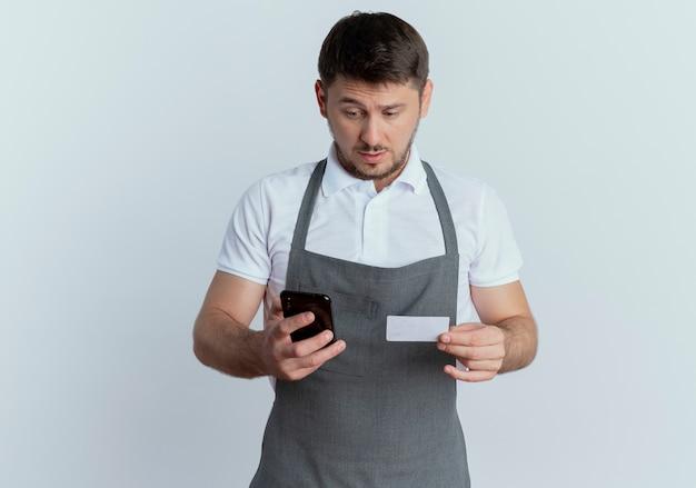 Homem barbeiro com avental loking confuso segurando um smartphone e um cartão de crédito em pé sobre um fundo branco