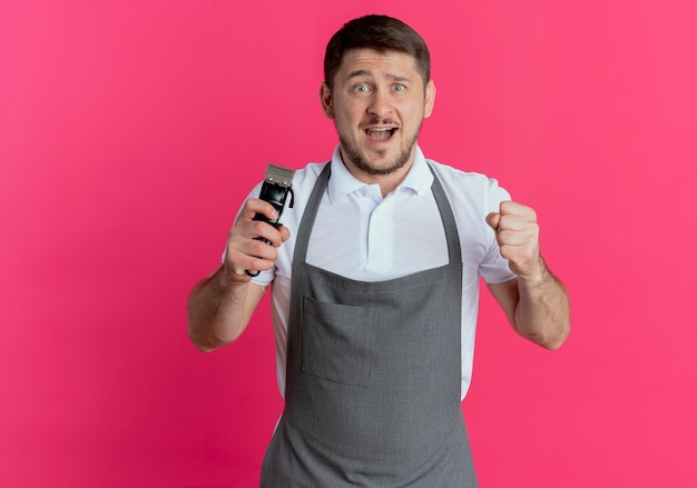 Homem barbeiro com avental segurando o aparador de barba, olhando para a câmera, punho cerrado, feliz e animado em pé sobre um fundo rosa