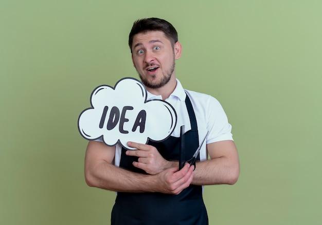 Homem barbeiro com avental segurando uma tesoura com pente e bolha do discurso assinar a ideia palavra surpresa em pé sobre a parede verde