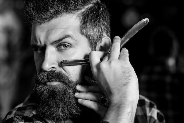 Homem barbeiro com navalha. cara brutal segurando ferramentas profissionais. barbearia. barbearia vintage, barbearia.