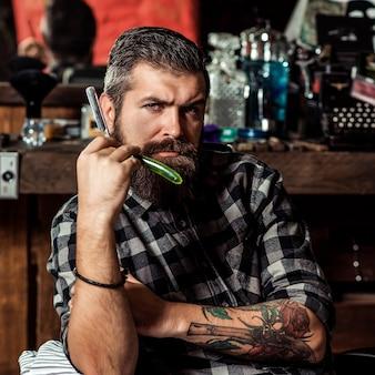 Homem barbeiro com navalha. cara brutal segurando ferramentas profissionais