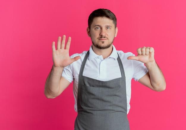 Homem barbeiro de avental aparecendo e apontando para cima com os dedos número seis, parecendo confiante em pé sobre a parede rosa
