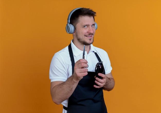 Homem barbeiro de avental com fones de ouvido segurando um aparador de barba e uma tesoura sorrindo maliciosamente em pé sobre uma parede laranja