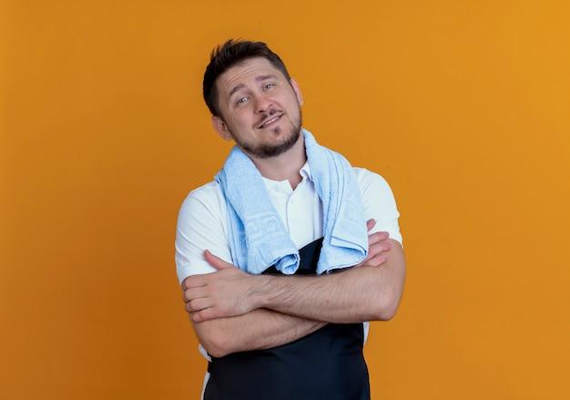 Homem barbeiro de avental com uma toalha ao redor do pescoço sorrindo confiante com os braços cruzados em pé sobre a parede laranja