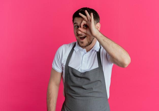 Homem barbeiro de avental indo bem cante com os dedos olhando através deste canto, feliz e alegre em pé sobre um fundo rosa