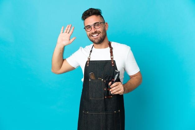 Homem barbeiro de avental saudando com a mão com expressão feliz
