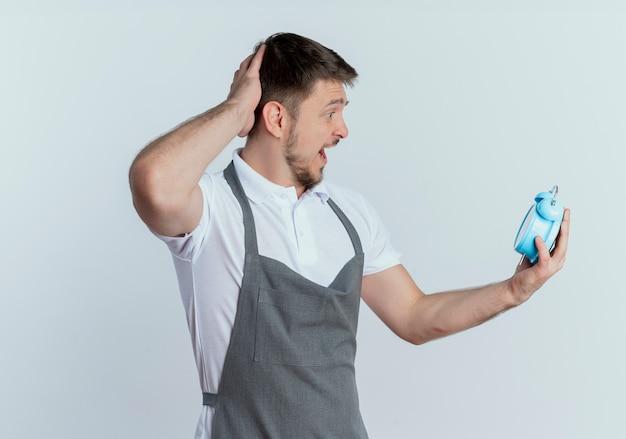 Homem barbeiro de avental segurando despertador olhando para ele confuso com a mão na cabeça