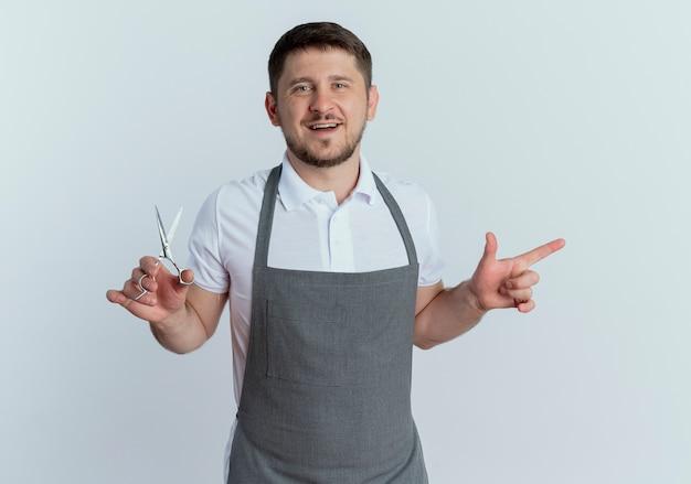 Homem barbeiro de avental segurando uma tesoura apontando com o dedo indicador para o lado sorrindo em pé sobre uma parede branca
