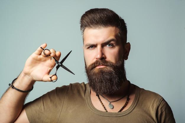 Homem barbeiro profissional com uma tesoura. cabeleireiro elegante na barbearia.