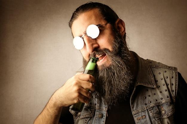 Homem barbudo, abrindo uma cerveja com os dentes