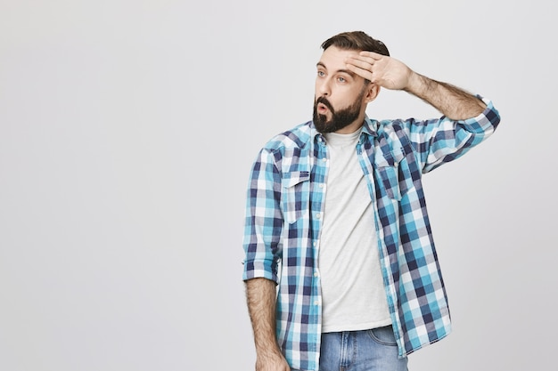 Homem barbudo adulto aliviado limpe o suor da testa e expire