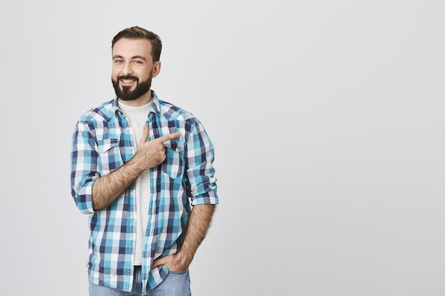 Homem barbudo adulto apontando o dedo para a direita, copyspace