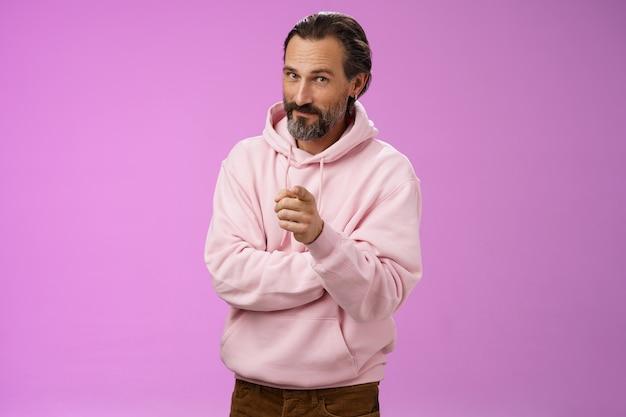 Homem barbudo adulto bonito e carismático confiante em um capuz cor-de-rosa elegante, convidando você a se juntar à empresa, sorrindo autoconfiante, indicando a escolha, tome a decisão nos escolhendo, fundo roxo.
