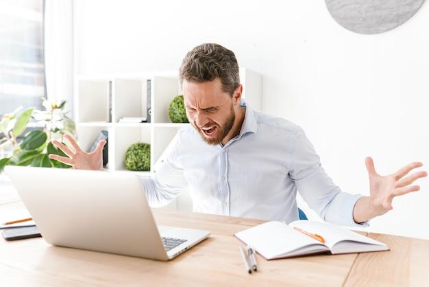 Homem barbudo agressivo sentado no escritório trabalhando