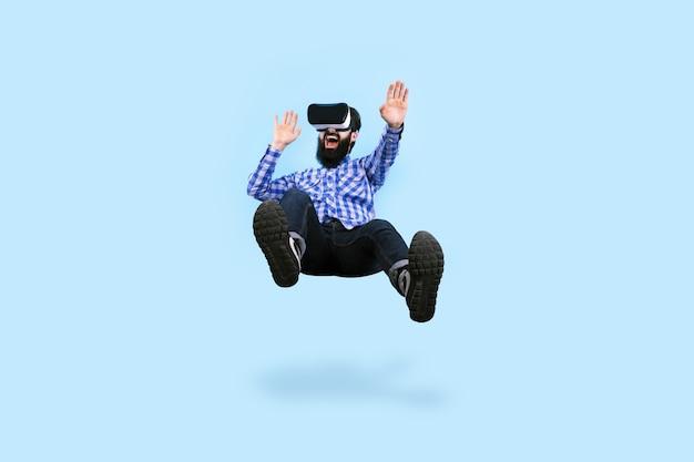 Homem barbudo alegre com óculos de realidade virtual levitando na parede azul