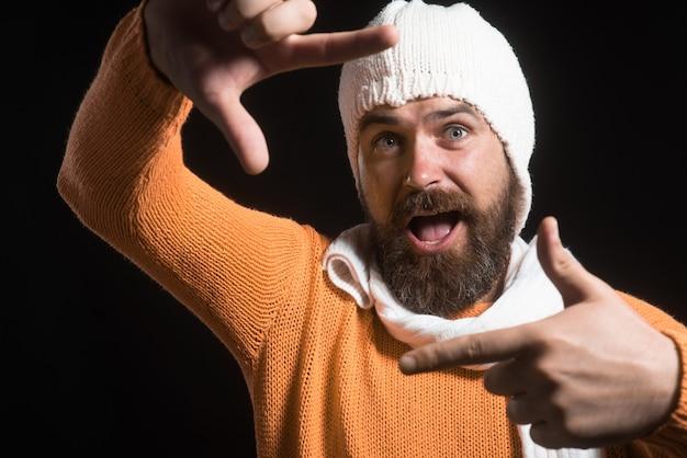 Homem barbudo alegre criando uma moldura com os dedos pessoas reais legais, aspirações criativas confiantes