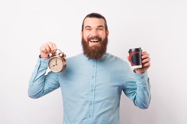 Homem barbudo alegre de camisa azul segurando um despertador e uma xícara de café