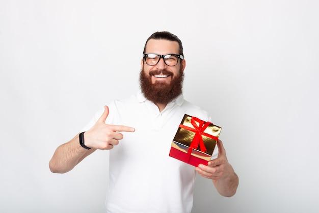Homem barbudo alegre e casual apontando para uma caixa de presente sobre fundo branco