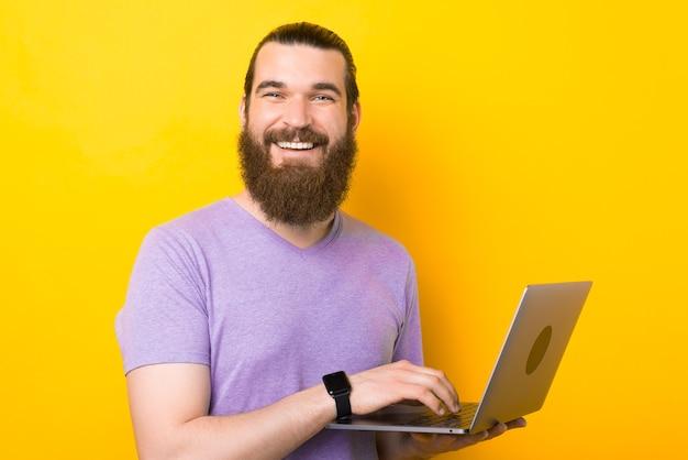 Homem barbudo alegre está digitando no laptop enquanto sorri para a câmera.