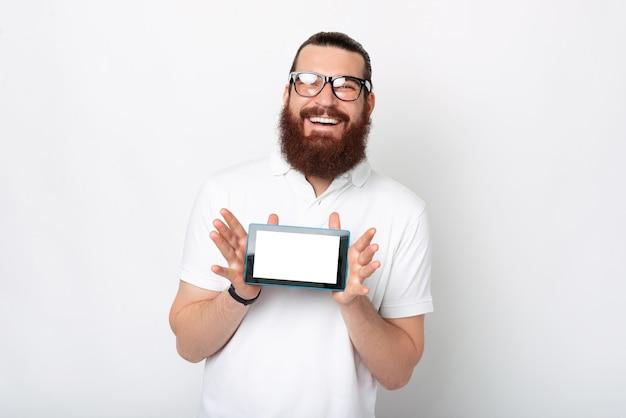 Homem barbudo alegre está mostrando a tela do tablet para a câmera.